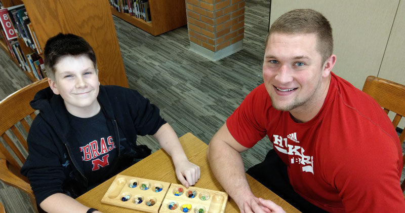 A male mentor and mentee playing a game of mancala